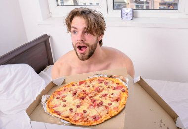 Man bearded handsome guy eating cheesy food for breakfast in bed. Food delivery service. Man likes pizza for breakfast. Who cares about diet. Guy holds pizza box sit bed in bedroom or hotel room