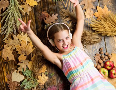 Enjoy music and relax. Happy childhood. Kid girl wooden background listen music headphones. Child listen music relaxing top view. Autumn melody concept. Autumn music playlist. Best songs about fall