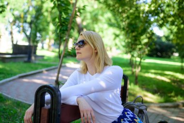 Time for yourself. Ways to give yourself break and enjoy leisure. Girl sit bench relaxing in shadow green nature background. Woman blonde take break relaxing in park. Find peaceful place in park