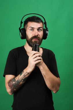 Man holds microphone on green background. Singer with beard