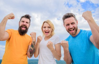 Celebrate success. We can do it. Ways to build successful team. Behaviors of winner team. Woman and men look successful celebrate victory sky background. Threesome stand happy with raised fists