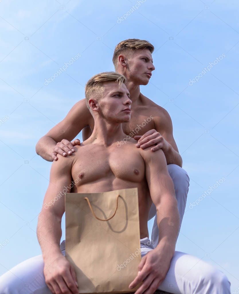 Healthy lifestyle concept. Men muscular athletes hold shopping bag sky background. Brothers buy eco healthy products. Hot sales and discount. Sales season. Guys attractive twins carry shopping bag