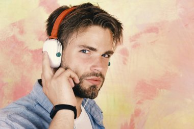 Blue eyed stylish hipster with smartphone. American handsome bearded guy with headphones. Musical lifestyle. European guy have fun time. Cheerful teenage dj listening songs via earphones