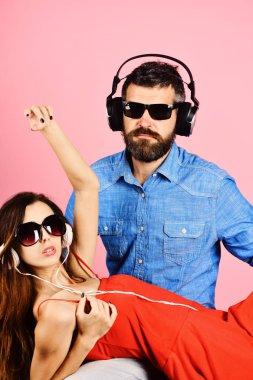 Couple in love wears plastic headphones and sunglasses