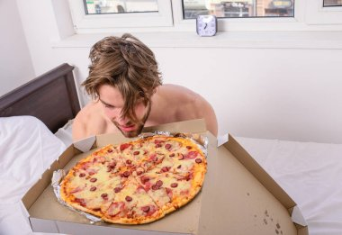 Who cares about diet. Man bearded handsome guy eating food pizza for breakfast in bed. Guy holds pizza box sit bed in bedroom or hotel room. Food delivery service. Man likes pizza for breakfast