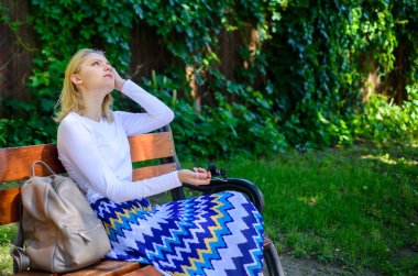Girl sit bench relaxing in shadow, green nature background. Woman blonde take break relaxing in park. Ways to give yourself break and enjoy leisure. Why you deserve break. Time for yourself