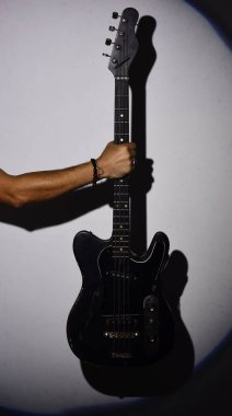 Electric guitar in male hand. Guitar player holds musical instrument