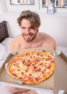 Food delivery service. Man bearded handsome bachelor eating cheesy food for breakfast in bed. Man likes pizza for breakfast. Break diet concept. Guy holds pizza box sit bed in bedroom or hotel room