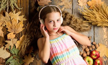 Happy childhood. Kid girl wooden background listen music headphones. Autumn melody concept. Child listen music relaxing top view. Autumn music playlist. Best songs about fall. Enjoy music and relax