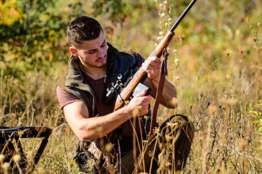 Hunter khaki clothes ready to hunt nature background. Hunting shooting trophy. Hunting hobby and leisure. Man charging hunting rifle. Hunting equipment concept. Hunter with rifle looking for animal