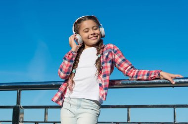 Young girl standing on bridge. Music lover. Happy childhood. Enjoying melody. Fashionable look. Music as favourite hobby. Headphones