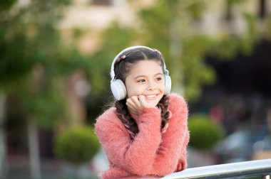 Funny cool stylish girl is listening to music and thinking about positiveness. Girl standing on the bridge with headphones. Tranquil influence of music. Nice girl in pink sweater enjoying song
