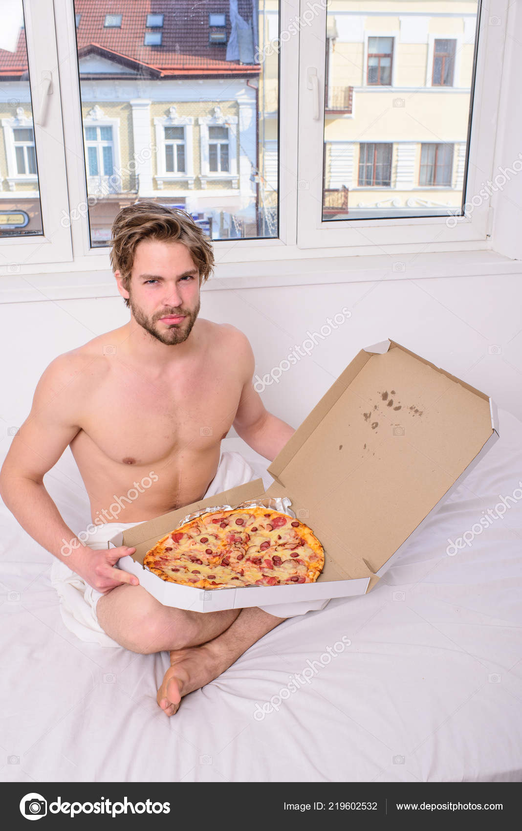 Guy Holds Pizza Box Sit Bed In Bedroom Or Hotel Room Food Delivery