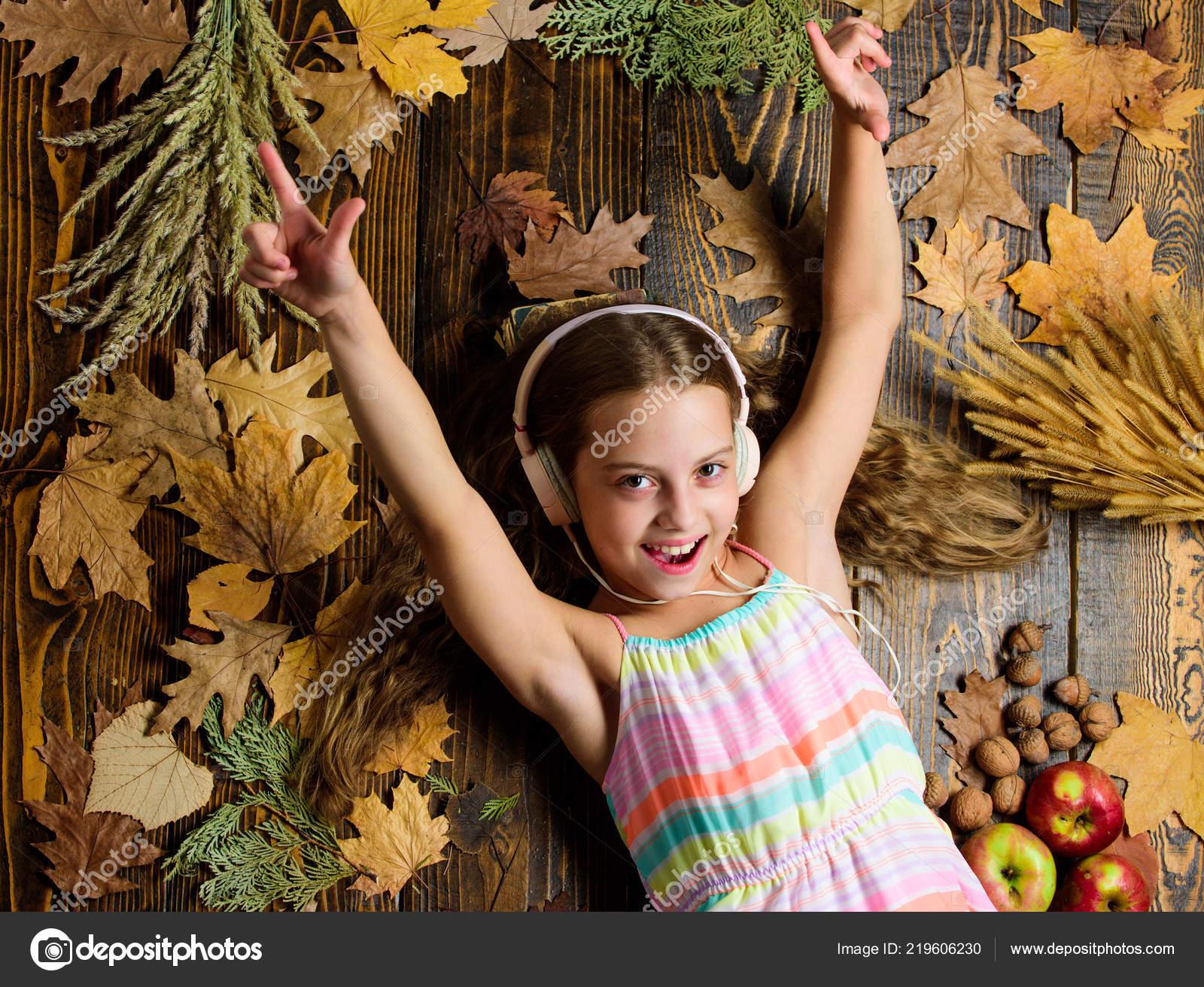 Kid girl wooden background listen music headphones child listen music relaxing top view autumn melody concept