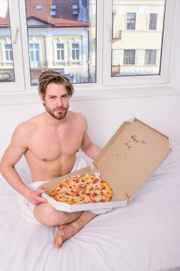 Guy holds pizza box sit bed in bedroom or hotel room. Food delivery service. Man likes pizza for breakfast. Bachelors nutrition. Man bearded handsome guy eating cheesy food for breakfast in bed