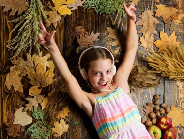Kid girl wooden background listen music headphones. Child listen music relaxing top view. Autumn melody concept. Happy childhood. Autumn music playlist. Best songs about fall. Enjoy music and relax