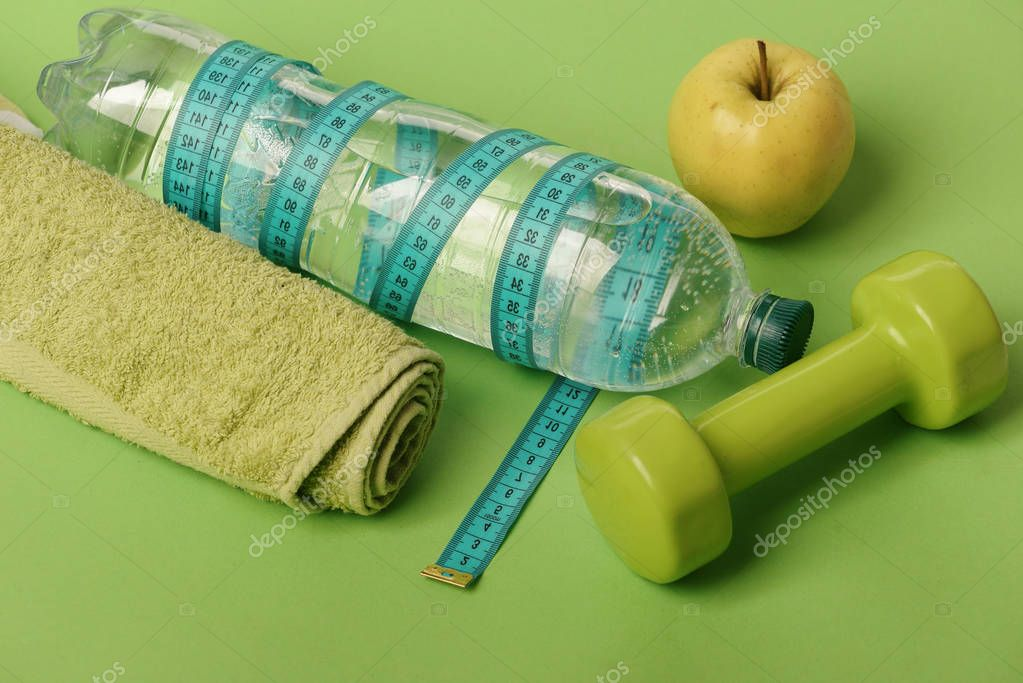 Dumbbell in bright green color, water bottle and measure tape
