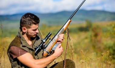 Man charging hunting rifle. Hunting equipment concept. Hunter khaki clothes ready to hunt nature background. Hunting shooting trophy. Hunter with rifle looking for animal. Hunting hobby and leisure
