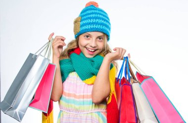 Girl cute face wear knitted autumn hat and scarf hold shopping bags white background. Shopping concept. Fall season sales. Sale and discount. Shopping mall profitable deal. Shopping on black friday