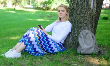 Give yourself break and enjoy leisure. Girl sit on grass lean on tree trunk relaxing in shadow green nature background. Woman blonde take break relaxing in park. Find peaceful place in park
