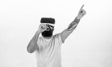 Hipster on busy face use modern technologies for entertainment or education. Man with beard in VR glasses, white background. Guy with VR glasses singing with virtual microphone. VR musician concept