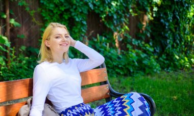 Feeling free and relaxed. Woman blonde take break relaxing in park. Why you deserve break. Ways to give yourself break and enjoy leisure. Girl sit bench relaxing in shadow, green nature background