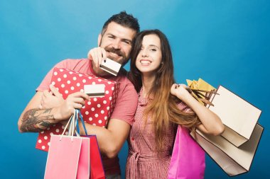Couple in love hugs holding shopping bags and credit cards