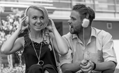 Man with woman enjoy music outdoor with urban background, defocused.