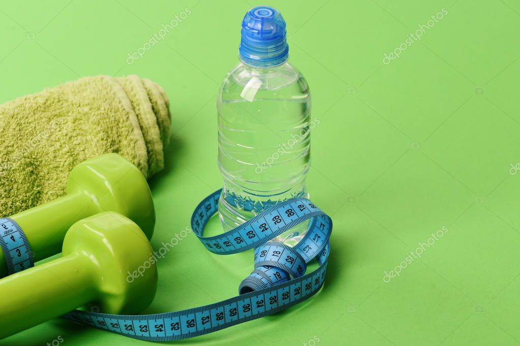 Dumbbells in bright green color, towel and twisted measure tape