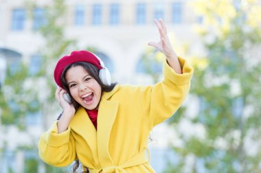 Little girl listening music enjoy favorite song. Girl with headphones urban background. Positive influence of music. Child girl french style outfit enjoying music. Childhood and teenage music taste
