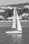 Lisabon, Portugalsko - 03 duben 2010: plachetnice v moři na městskou krajinu. Plachetnice s bílou plachtou plachtění podél pobřeží moře. Letní dobrodružství a aktivní dovolenou. Plachetní jachty a toulavost