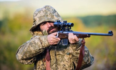 Hunting season. Guy hunting nature environment. Bearded hunter rifle nature background. Experience and practice lends success hunting. Hunting big game typically requires tag each animal harvested