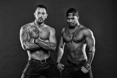 Tattoo is symbolic. Sexy men with muscular torso. Muscular men with fashionable tattoo style. Brutal macho style. We are sexy, black and white