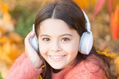 Give in to the groove. Happy child wear headphones. Little music fan on autumn day. Happy little girl in autumn. Little girl listen to music. Everyone deserve music
