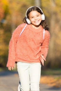 Keep a song in your heart. Little girl listen to music. Little music fan on autumn day. Happy little child in autumn. Happy child with headphones. Drift into the music
