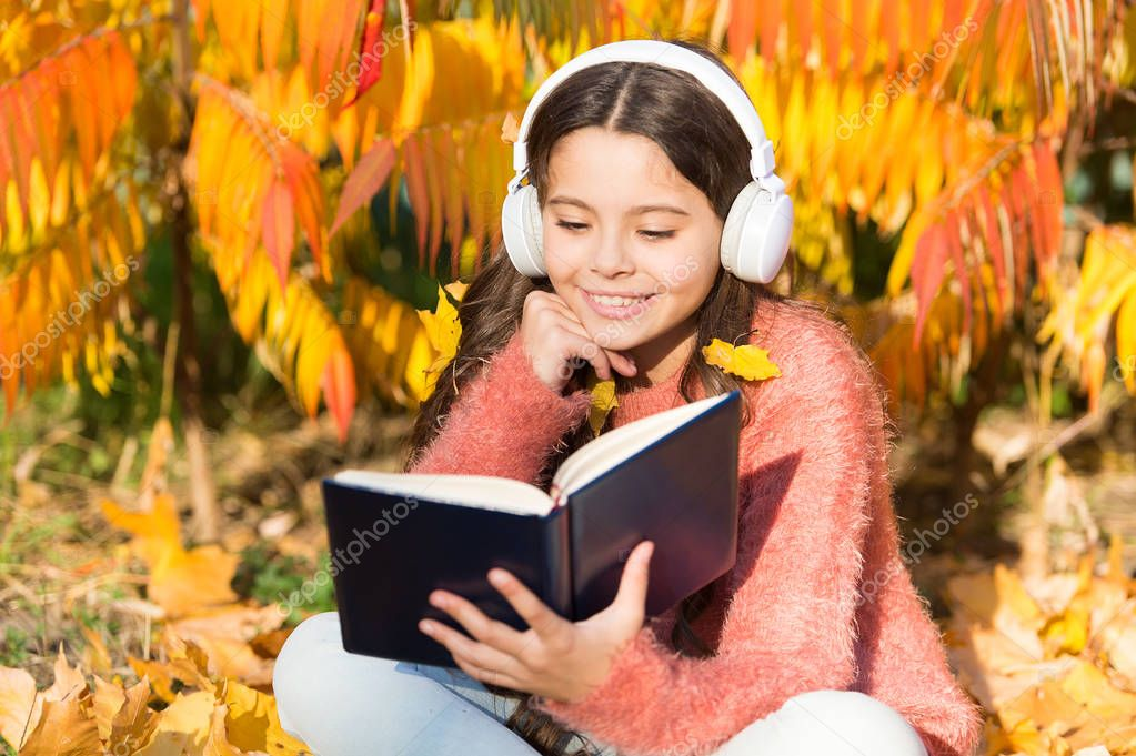 My autumn story. Little child listen to ebook in headphones. Little child enjoy learning in autumn park. Ebook holds much that is important to me