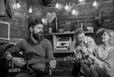 Bearded man singing serenade for his wife, love and romance concept. Couple celebrating anniversary or St. Valentine Day. Family spending lovely evening together. Man with trendy beard playing guitar