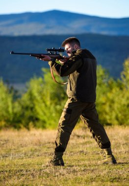 Man rifle for hunt. Hunter khaki clothes ready to hunt hold gun mountains background. Hunter with rifle looking for animal. Hunting shooting trophy. Mental preparation for hunting individual process