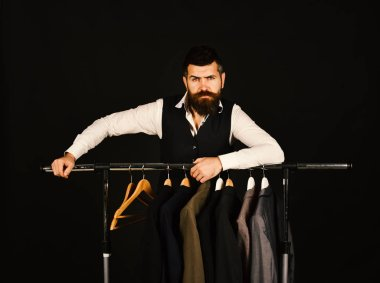 Man with beard in vest by clothes rack.