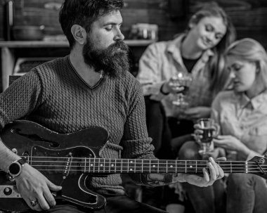 Guitarist playing at birthday, celebration concept. Bearded man performing guitar solo. Man with stylish beard entertaining guests at party. Musician spending lovely evening with wife and daughter