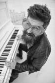 Fotografie Mann in riesige rote Sonnenbrille beim Klavierspielen. Mann, fröhlich Pianist spielt. Comic-Künstler-Konzept. Mann in Lederjacke sitzt in der Nähe von Klavier Musikinstrument in weißen Innenraum auf Hintergrund
