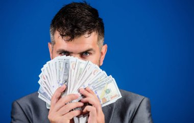 Easy cash loans. Businessman got cash money. Richness and wellbeing concept. Get cash money easy and quickly. Smell of money. Man formal suit hold pile of dollar banknotes blue background.