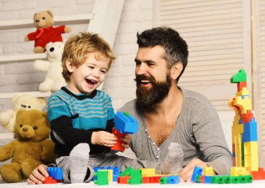 Boy and man play together. Dad and kid with toys