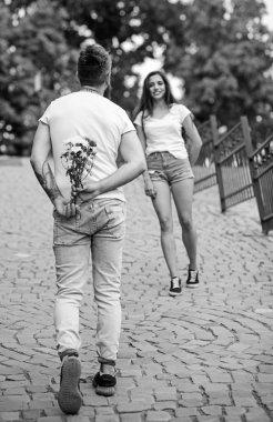Guy prepared surprise bouquet for girlfriend. Gentlemans manners. Man hides flower bouquet behind back while wait girl romantic date. Couple meeting for date park background. Bouquet always good idea