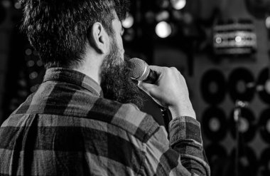 Musician with beard singing song in karaoke, rear view. Rock singer concept. Guy likes to sing in dark karaoke hall. Man in checkered shirt holds microphone, singing song, karaoke club background