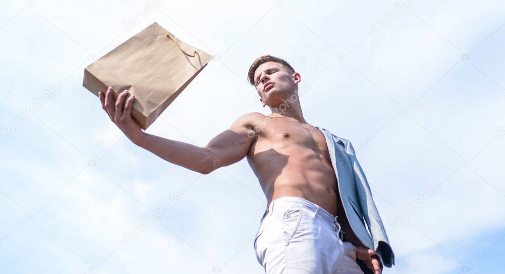 Hot sales and discount. Guy attractive macho carry shopping bag made out of brown paper. Take this package. Sales season. Eco products shop. Man muscular athlete hold shopping bag sky background