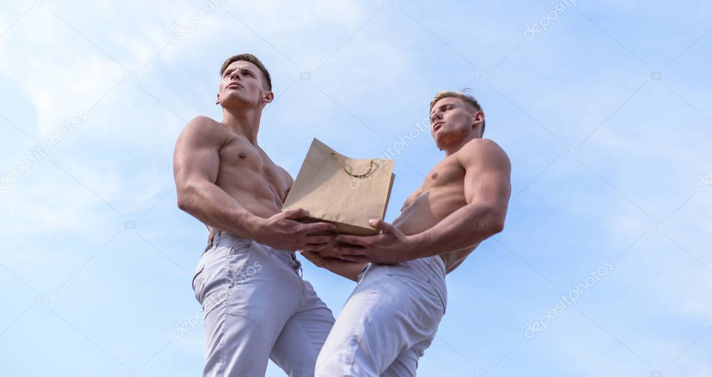 Guys attractive twins carry shopping bag made out of brown paper. Men muscular athletes hold shopping bag sky background. Brothers buy eco healthy products. Hot sales and discount. Sales season