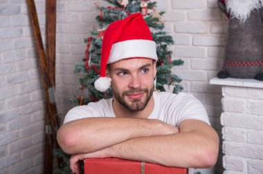 The morning before Xmas. happy santa man. delivery christmas gifts. online christmas shopping. New year scene with tree and gifts. man in santa hat hold christmas present. Christmas composition