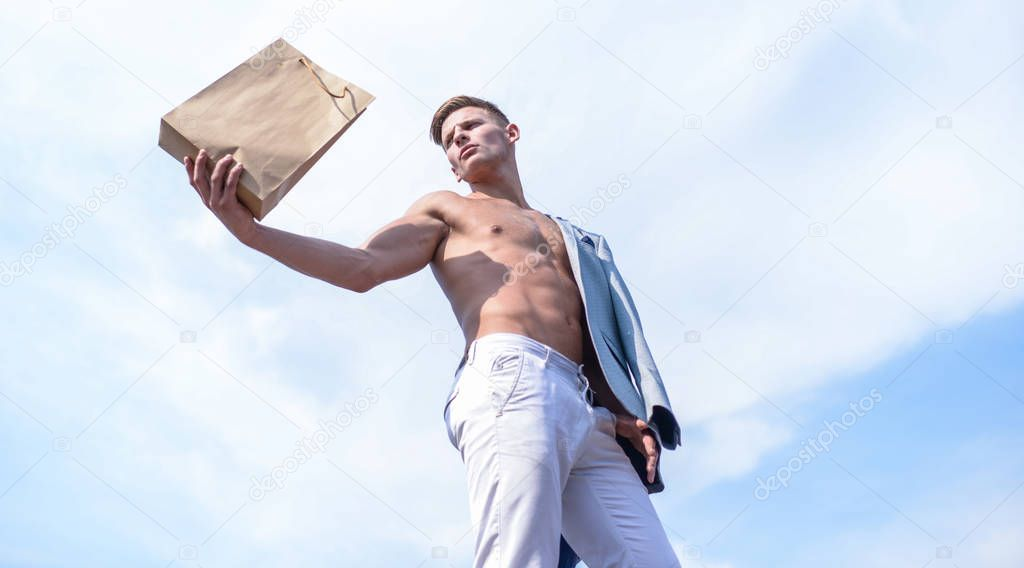 Guy attractive macho carry shopping bag made out of brown paper. Take this package. Sales season. Eco products shop. Man muscular athlete hold shopping bag sky background. Hot sales and discount
