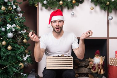 The morning before Xmas. delivery christmas gifts. happy santa man. online christmas shopping. New year scene with tree gift. man in santa hat hold christmas present. Merry Christmas. what is this